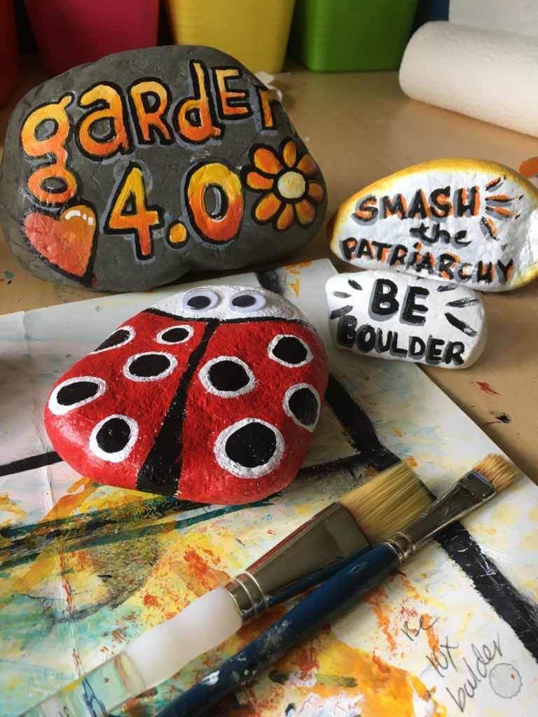 "image of some painted rocks - one is a lady bug, one says ""garden 4.0"", one says, ""smash the patriarchy"" and one says ""be boulder"" which is a hilarious pun because rocks are boulders"